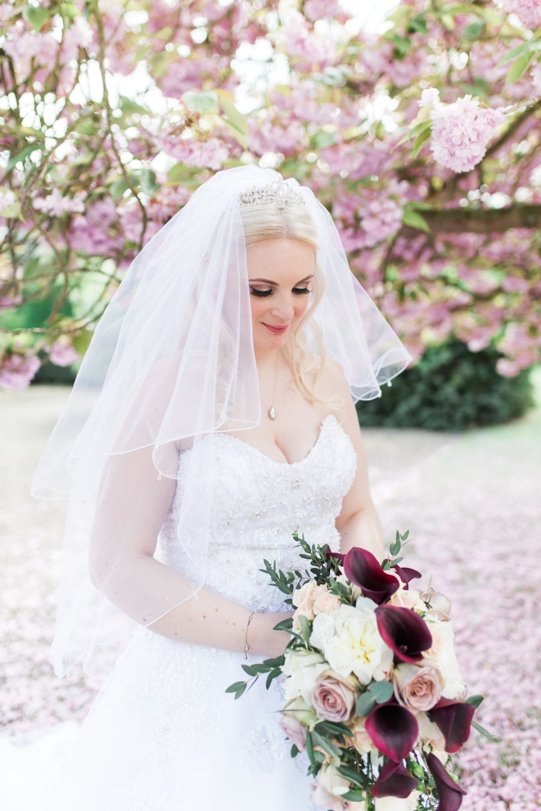 Bride under the blossom tree at Down Hall wedding venue
