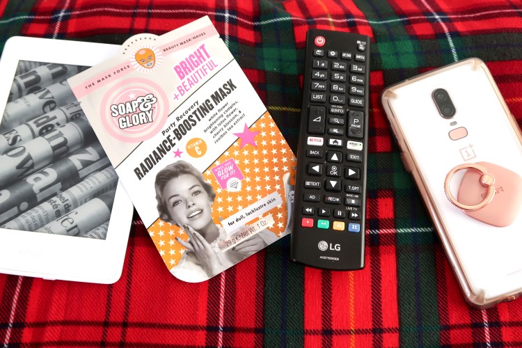 Header image of kindle, facemask, tv remote and phone laying on tartan fabric background