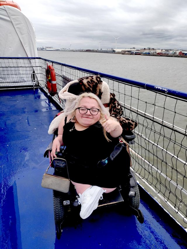 Gem on ferry with her thumb up and smiling