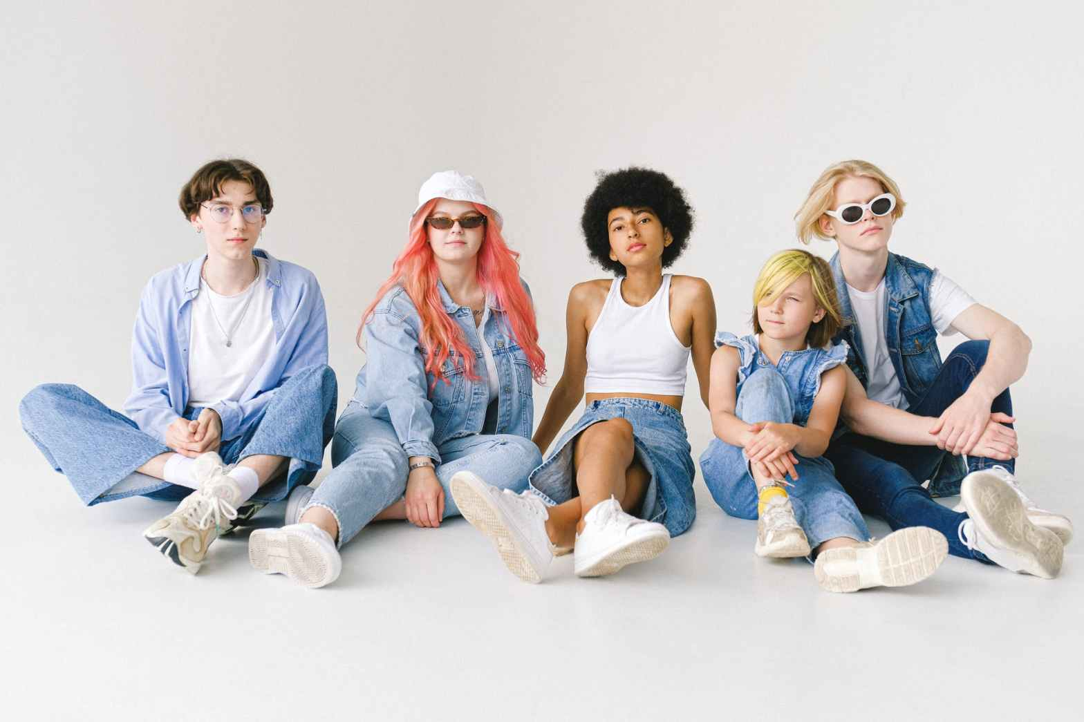 stylish multiracial models in denim outfits sitting on floor