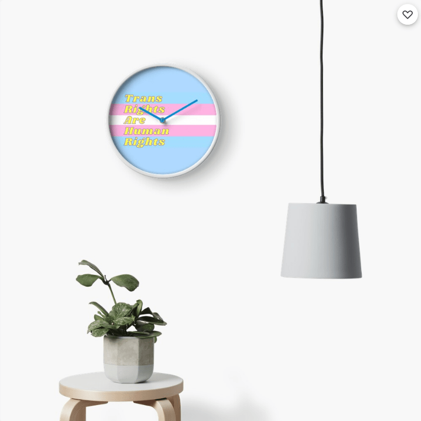 """A round clock with the trans flag colours printed on it, and """"trans rights are human rights""""."""