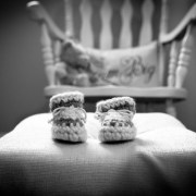 baby knitted moccasins featured with iconic rocking chair and teddy in background