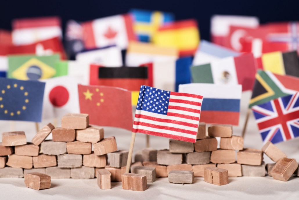 Small representations of flags of the world with the American flag in the foreground amidst a pile of bricks representing a wall