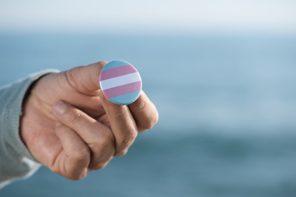 closeup of a young caucasian person outdoors showing a badge patterned with a transgender pride flag, in front of the ocean