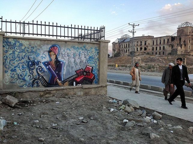 Men on a street in Kabul looking at a mural by Afghan artist Shamsia Hassani