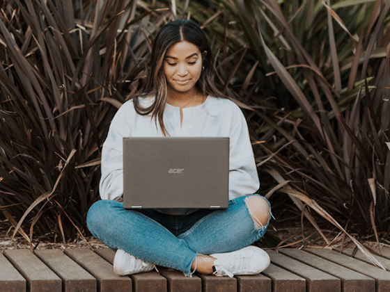 Woman sitting with a laptop completing communications and marketing certifications