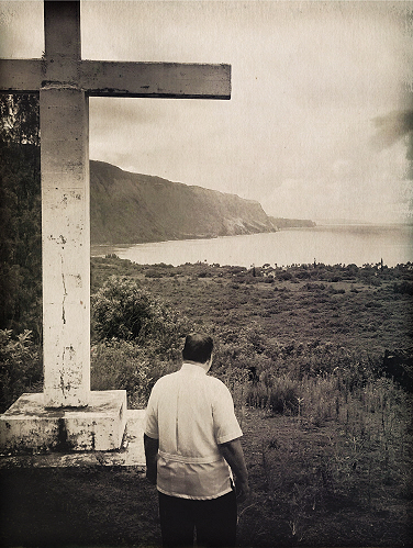 Father William F. Petrie, sscc, looking over Kalaupapa Settlement from the cross atop the Kauhako crater.