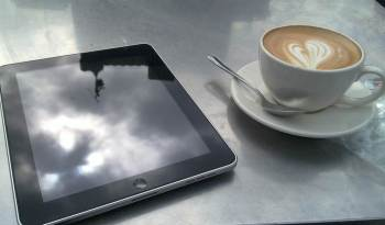 A tablet and a cup of coffee on a table.