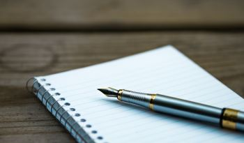 Close up of a pen and a notebook.