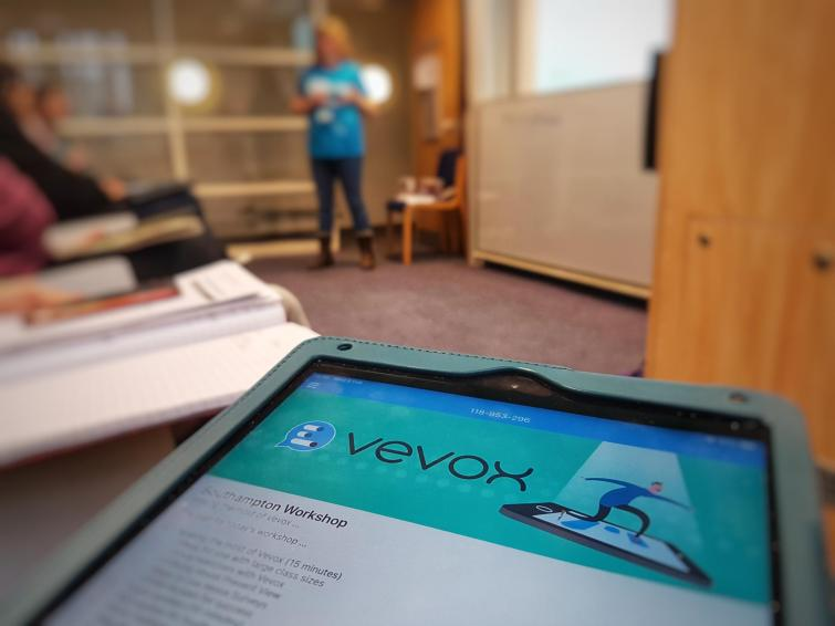 Vevox app on mobile with session presenters in background