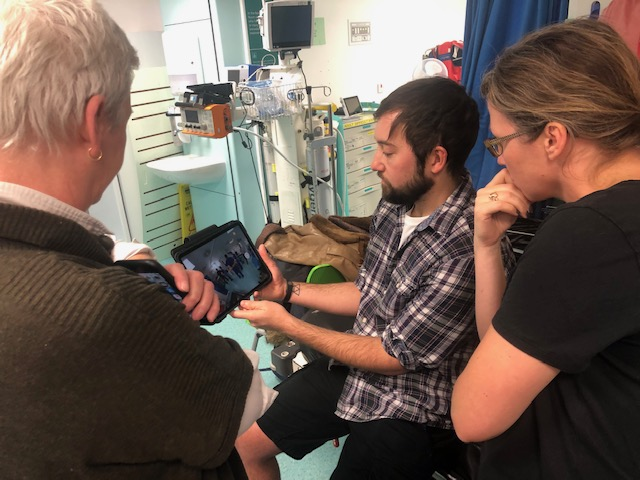 Three people standing in a hospital bed bay, looking at an ipad screen.