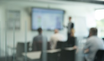 A classroom surrounded by glass, where the occupants are out of focus, giving an impression of a lesson taking place.
