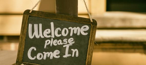 A blackboard sign with Welcome please come in, written on it.
