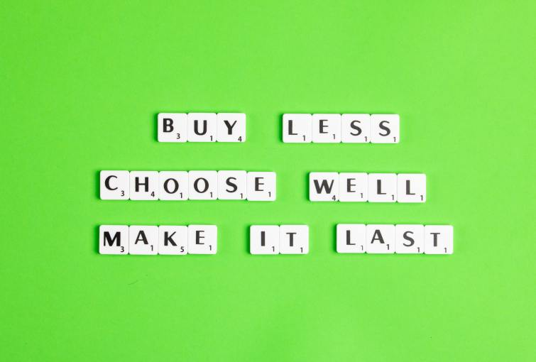 Scrabble letters on a bright green background spell out the words Buy less, choose well, make it last.