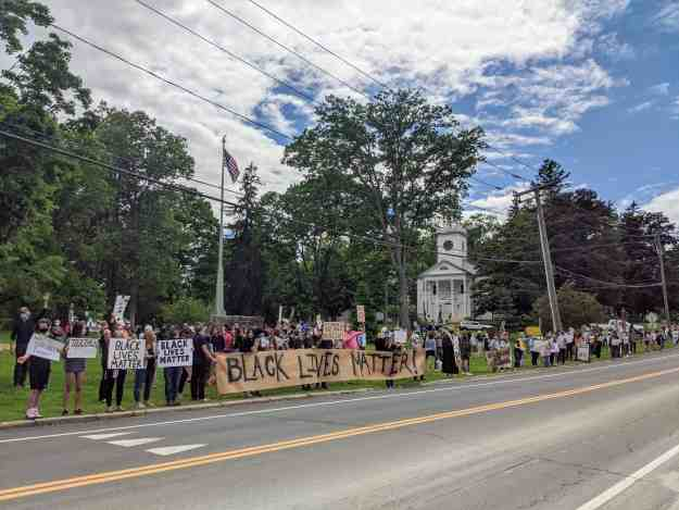 Black Lives Matter at a small town protest hold signs while lining Route 44