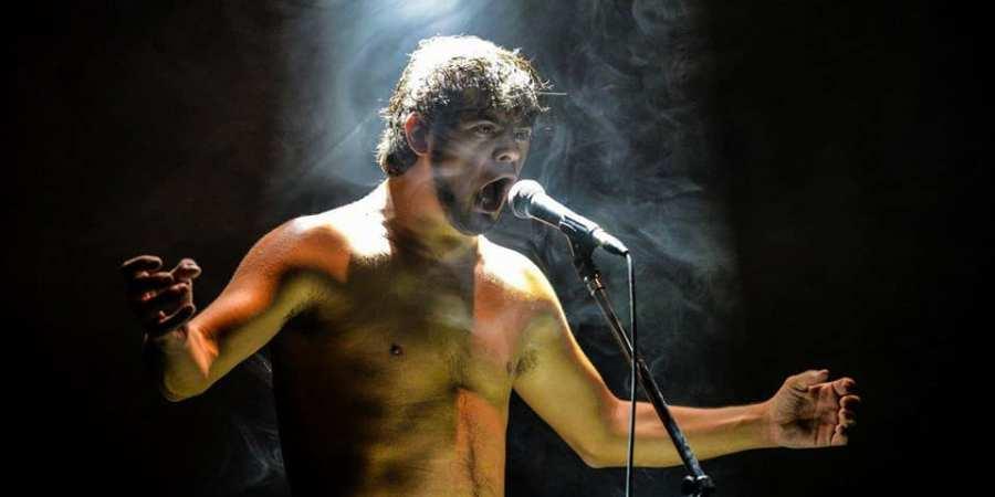 un artiste torse nu devant un micro, les bras ouverts