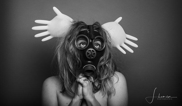 Une femme porte un masque à gaz et a deux gants en latex gonflés comme des oreilles de Mickey