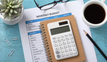 Monthly budget concept with white calculator and coffee cup on blue wooden table