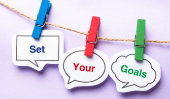 Set your goals paper bubbles with clip hanging on the line against purple background.
