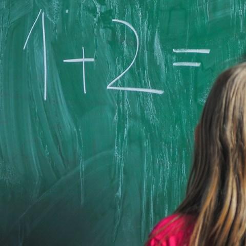 Girl doing math at a chalkboard