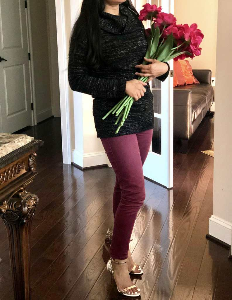 girl wearing cowl neck knit tunic and holding flowers