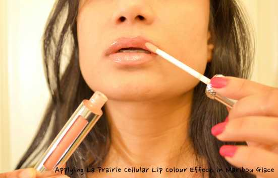 Applying La Prairie Cellular Lip Effect in Maribou Glace alone on lips