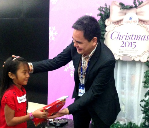 SM Supermalls VP for Mindanao Operations Oliver Tiu hands a gift to a ChriSMiles beneficiary.