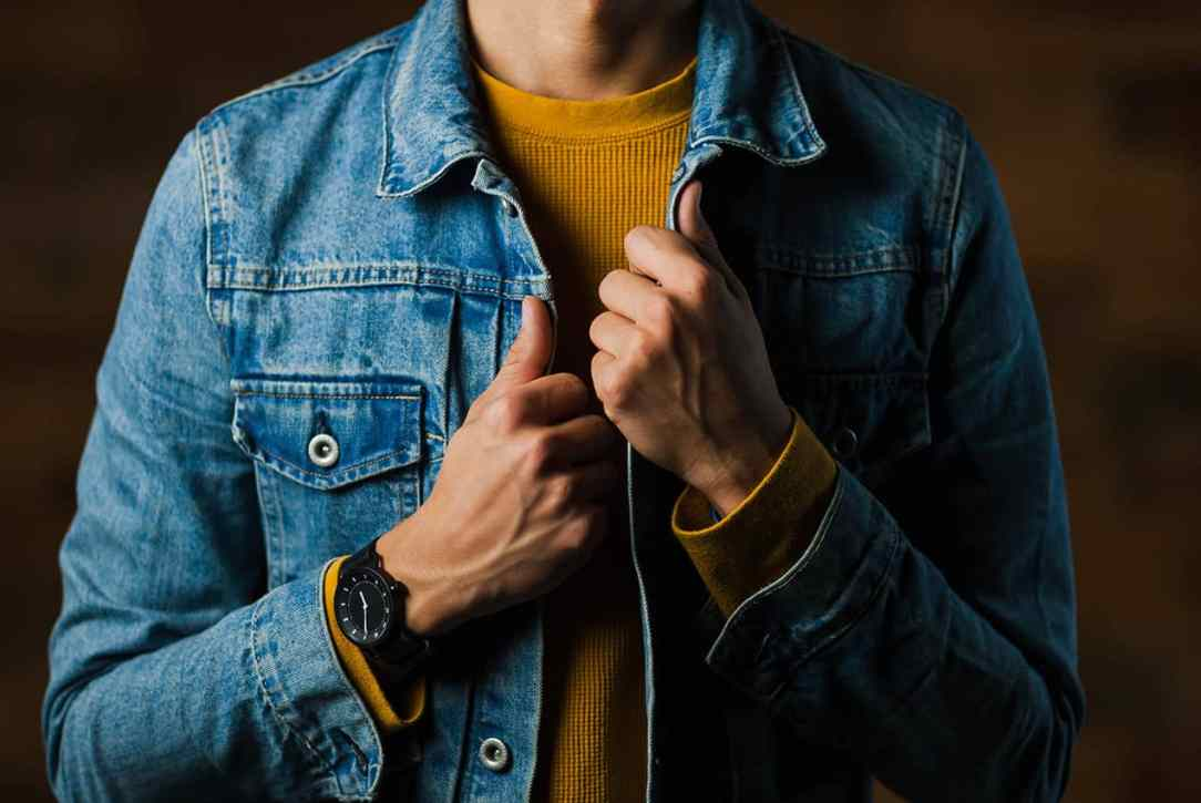 A man wearing a yellow sweater in combination with a denim jacket.