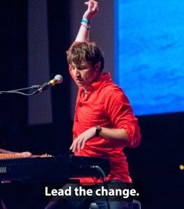 Gentry Bronson in red shirt live on stage with hand in the air leading the band behind him