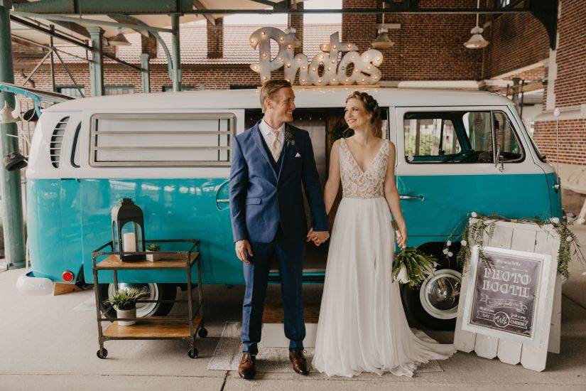 Bride and Groom in blue suit posing in front of fun old bus photo booth