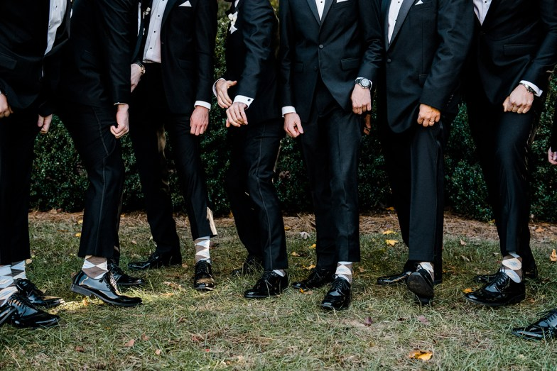 groom and groomsmen in black tuxedos showing off socks