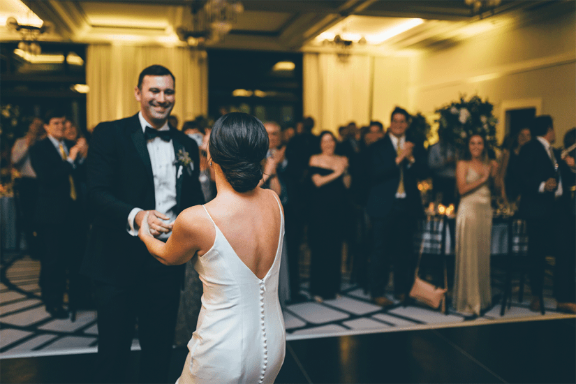 bride and groom in black tuxedo sharing first dance