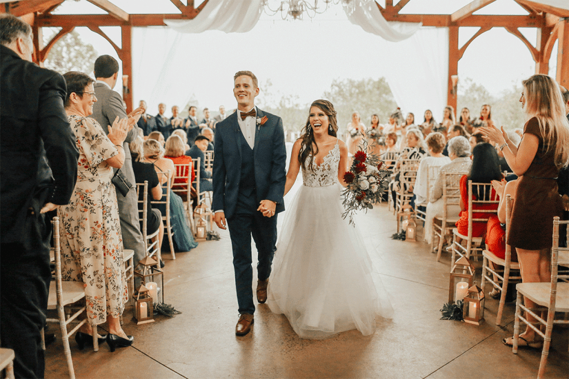 bride and groom in blue suit during wedding recessional