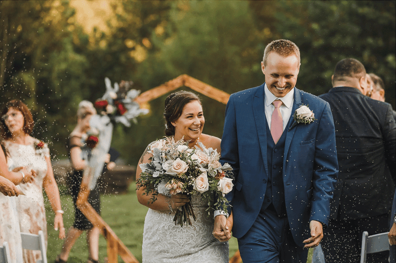 bride and groom in blue suit during recessional