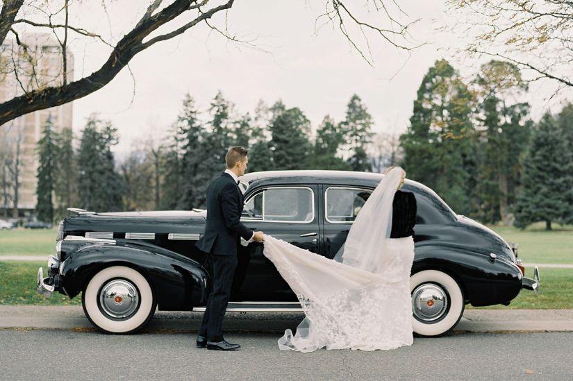 bride and groom in black tuxedo getting into old car
