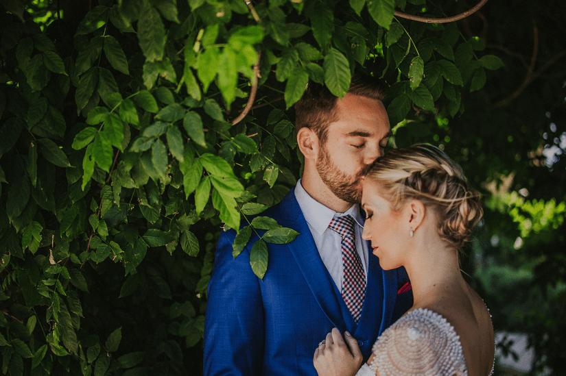 groom in blue suit kissing bride