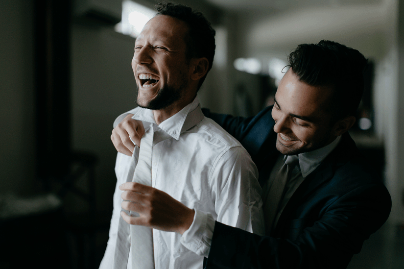 best man helping groom with his tie