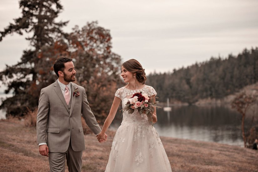 Bride and groom in gray suit holding hands