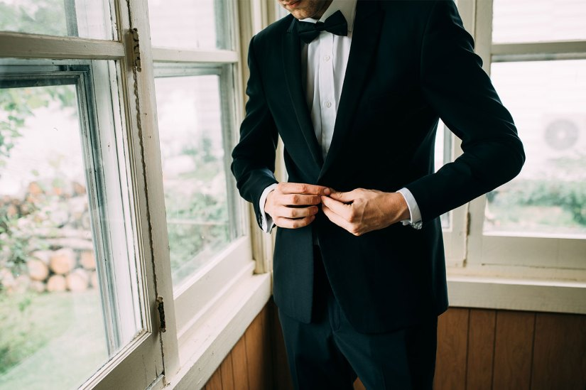 Groom in black tuxedo getting ready
