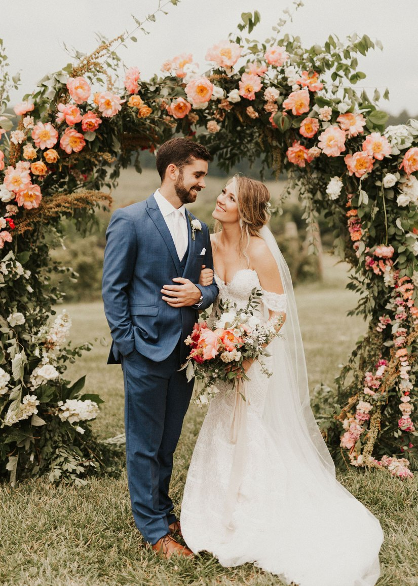 bride and groom in blue suit in front of flower arbor
