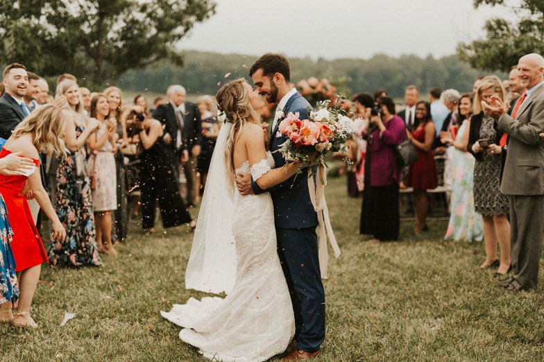 bride and groom kissing during sendoff