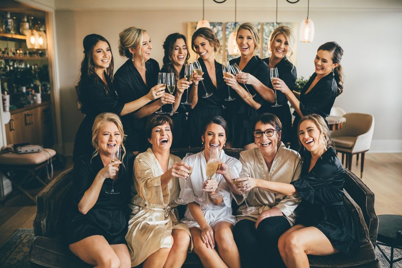 Bride and bridesmaids getting ready and posing with champagne