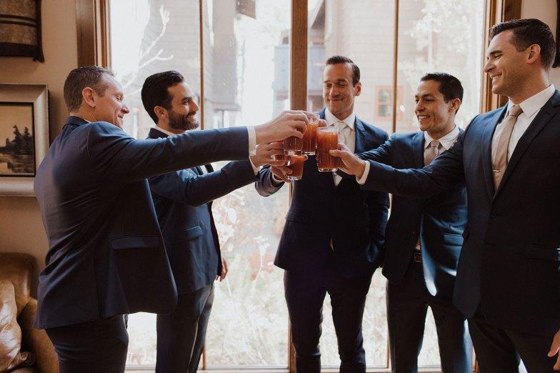 groom and groomsmen in blue suits toasting