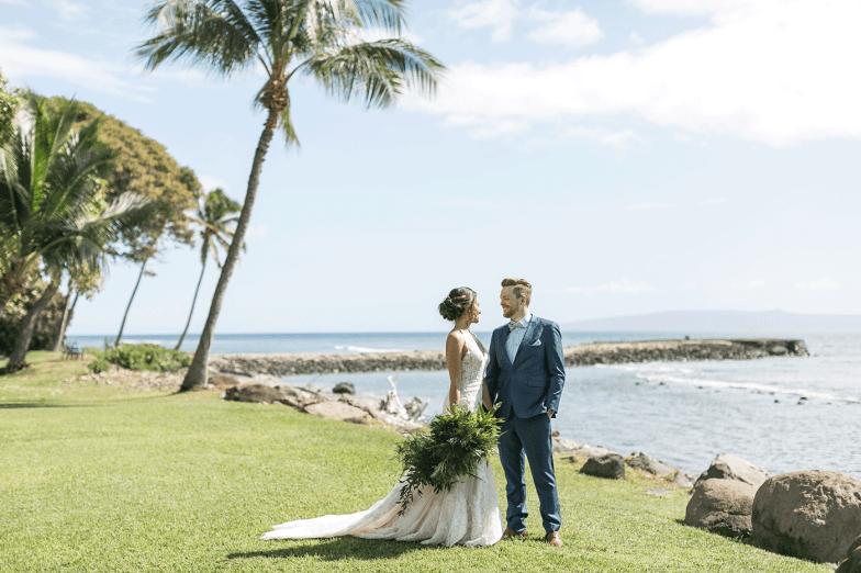 Bride and groom in blue suit on hawaii beach