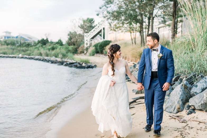 bride and groom in blue suit walking on beach