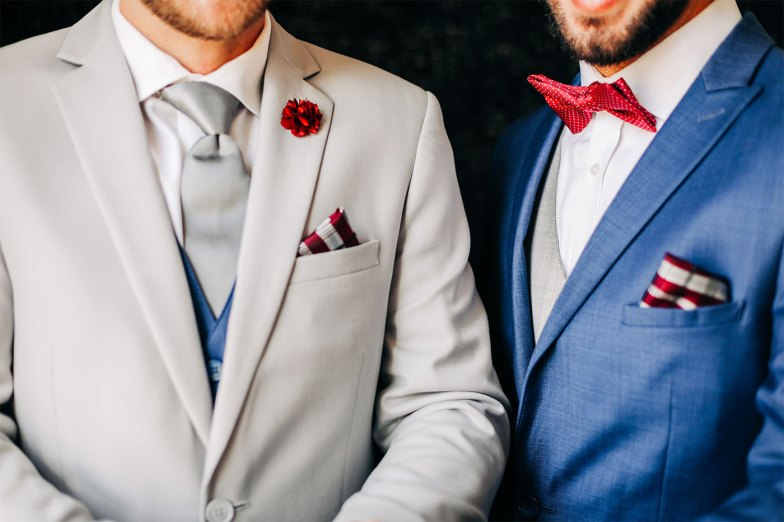 two grooms in a gray suit and a blue suit with red accents