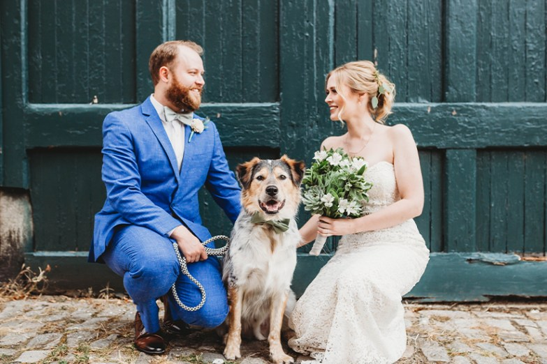 married couple with dog at wedding