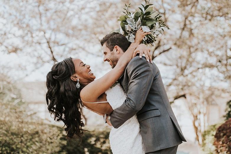 happy groom holding bride on wedding day