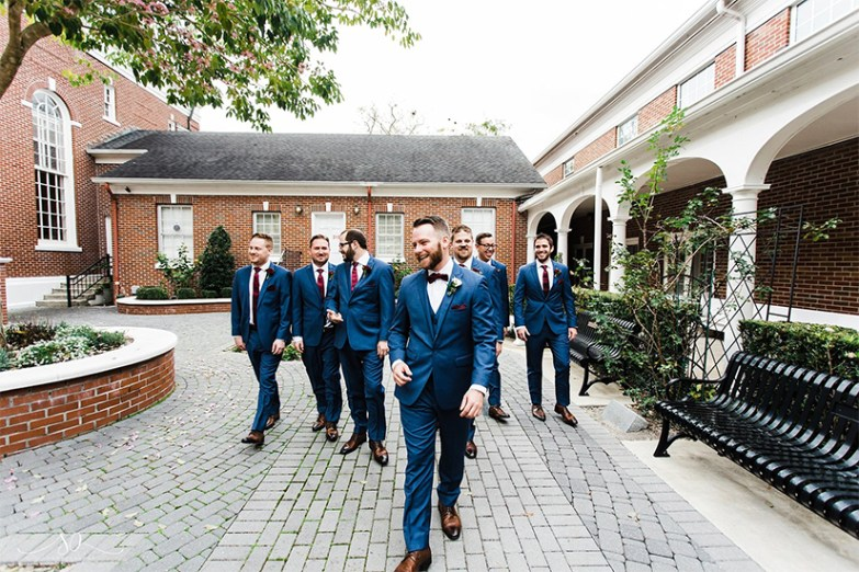 Group on groomsmen in blue generation tux suits walking
