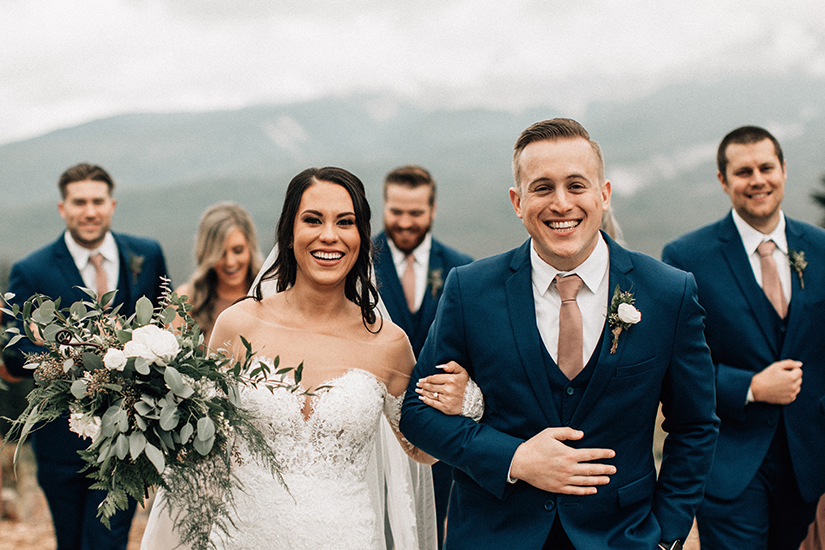 bride and groom laughing with groomsmen in generation tux suits winter wedding